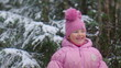 Little girl with shovel playing in snow forest