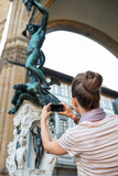 Young woman taking photo of statue perseus in florence poster