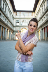 Young woman near uffizi gallery pointing in florence, italy