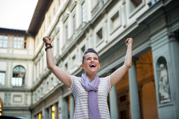 Happy young woman near uffizi gallery rejoicing in florence