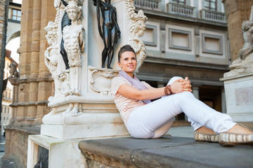 Young woman sitting in loggia dei lanzi in florence, italy