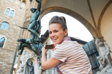 Young woman taking photo of statue perseus in florence