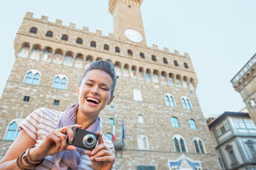 Portrait of happy young woman with photo camera in firenze