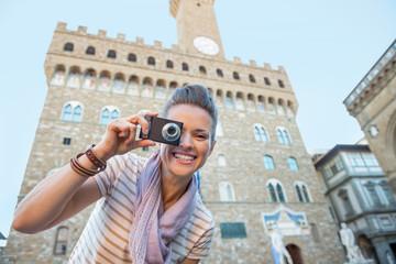 Happy young woman taking photo in front of palazzo vecchio