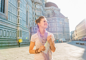 Happy young woman with map in front of cattedrale  in florence