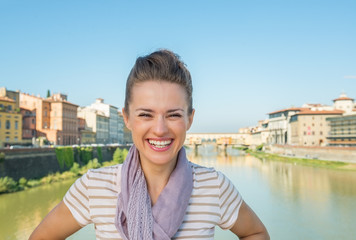 Portrait of smiling young woman standing on bridge  in florence