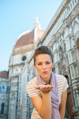 Portrait of happy young woman blowing kiss  in florence