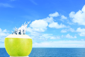Green coconut with water splash on the beach