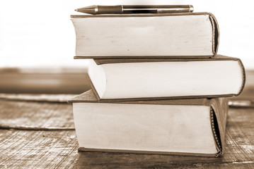 Old books on wooden table - vintage sepia look