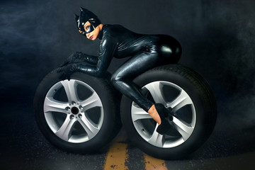 Sexy female in black catwoman costume on motorcycle