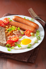 english breakfast with fried egg sausages bacon tomatoes beans