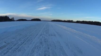 Moving along ice road on big lake