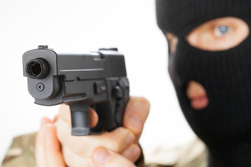 Man in black mask holding gun in front of him