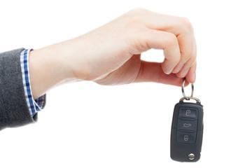 Male hand giving car keys - studio shot over white background