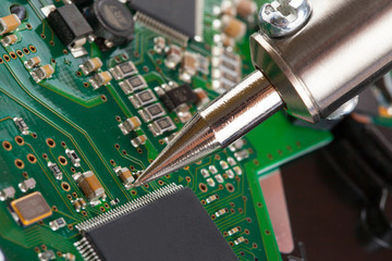 Soldering iron and microcircuit - closeup studio shot