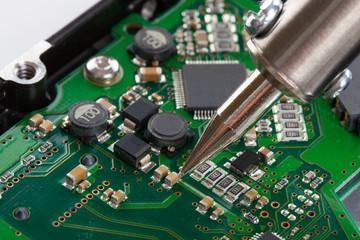 Studio shot of soldering iron and microcircuit
