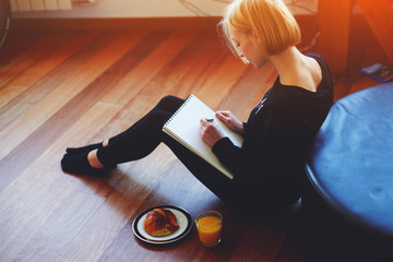 Beautiful girl writes her diary sitting at living room