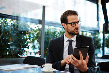 Smart attractive businessman holding tablet pc having a coffee