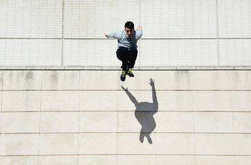 Male parkour free runner jumping forward from high rooftop