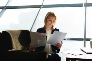 Young businesswoman examining paperwork before meeting