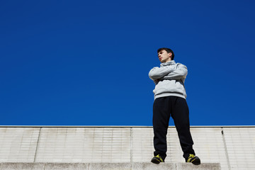 Male tracer standing on edge of a high building against sky