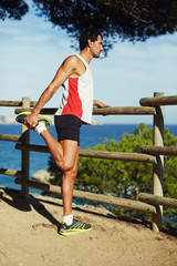 Mature man stretching his legs before a run outdoors along sea