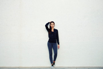 Sporty young woman standing against a white background outdoors