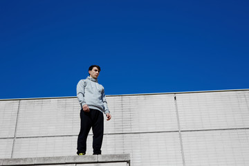 Male tracer standing on the edge of a high industrial building