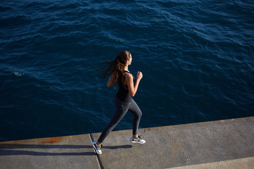 Young woman out jogging along the coastline at sunny day