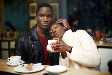 Young beautiful couple in love having coffee in cafe shop