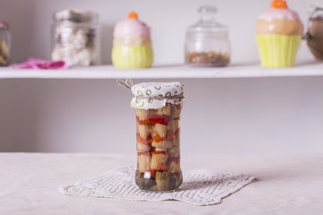 a small glass jar with conservation, corn, peppers, mushrooms