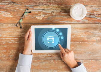 close up of hands with tablet pc and shopping cart