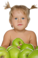 Little beautiful girl with green apples