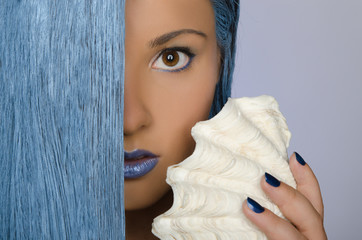 young woman with long blue hair and shells