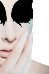 face and hand of woman with black white makeup