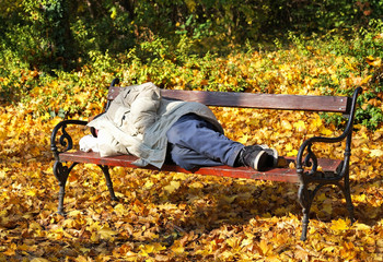 Homeless man is sleeping on a bench in the woods