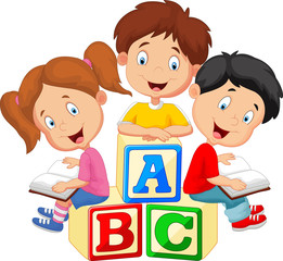 Children reading book and sitting on alphabet blocks