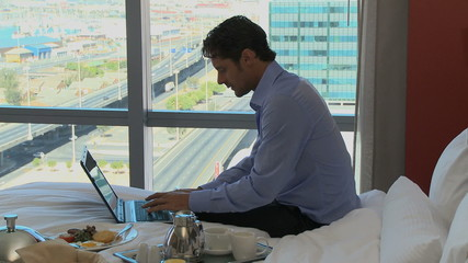 LS PAN OF A BUSINESSMAN WORKING IN HIS HOTEL ROOM