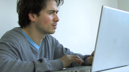 MS OF A MAN TYPING ON A LAPTOP