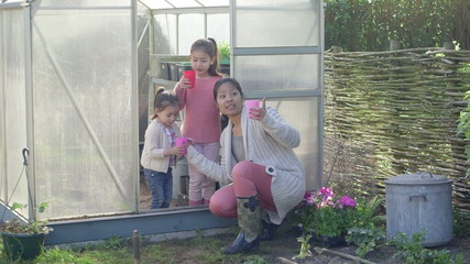 Mother with daughter near greenhouse