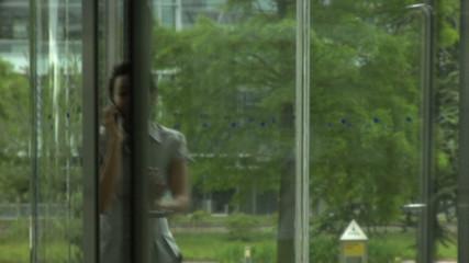 MS FEMALE WALKING THROUGH DOOR IN OFFICE ON PHONE