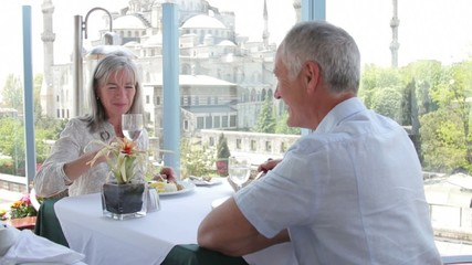 Senior couple enjoying a glass of wine and lunch overlooking the Blue Mosque, Istanbul, Turkey