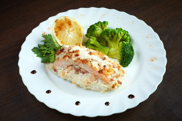 Serving of tasty baked fish with vegetables