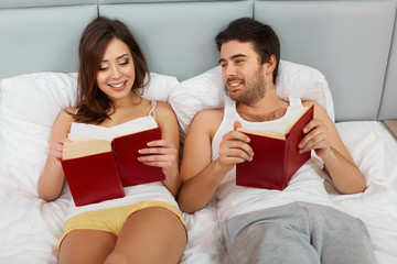 Happy Couple Sitting in Bed Reading Books at Home