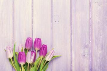 Purple tulip bouquet over wooden table