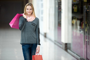Smiling female in shopping mall walking with paper bags