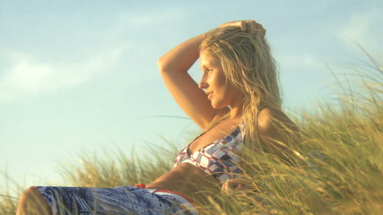 MS OF A YOUNG WOMAN LYING DOWN AMONGST MARRAM GRASS ON A BEACH