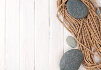 Wooden background with marine rope and sea stones