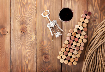 Wine bottle shaped corks, glass of red wine and corkscrew