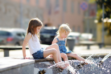 Two sisters having fun in a city fountain